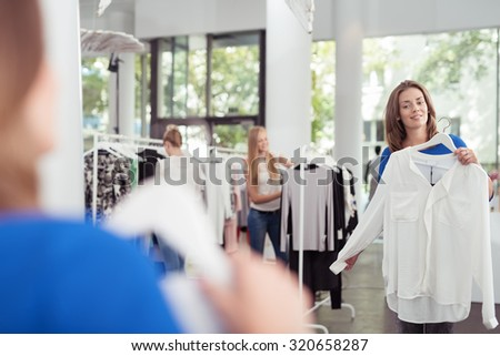 Stylish Young Woman Checking Out White Shirt In Front of a Mirror Inside a Clothing Store. - stock photo
