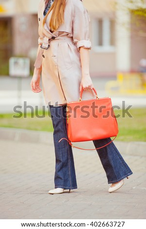 Stylish young woman in a beige trench, jeans flared and high-heeled shoes on the streets. Fashion. - stock photo