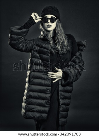 Stylish young woman in a down coat and knit cap. - stock photo