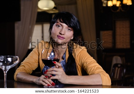 Stylish young woman in a nightclub or bar sitting drinking a large glass of red wine looking directly at the camera - stock photo