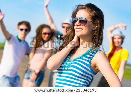 stylish young woman in sunglasses on the background of blue sky and friends - stock photo