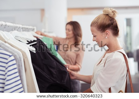 Stylish Young Woman Looking at the Clothes Hanging on Rail Inside the Clothing Store. - stock photo