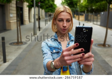 Stylish young woman photographing urban view with mobile phone camera during summer journey,gorgeous female tourist taking picture with her smart phone while standing outdoors in urban setting  street - stock photo