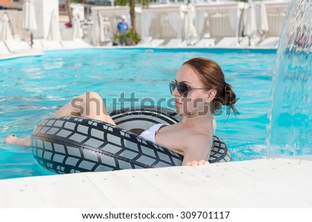 Stylish young woman relaxing in a swimming pool lying floating in a comfortable tube as she enjoys her summer vacation - stock photo