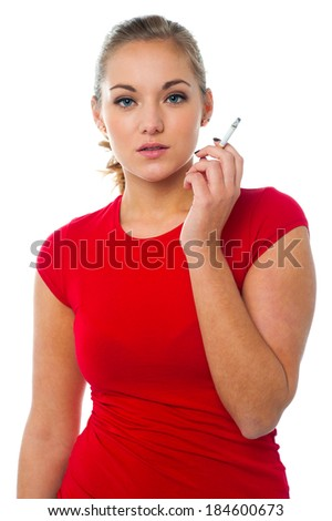 Stylish young woman smoking a cigarette - stock photo