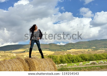 Stylish young woman stands on stack of hay on sunny day in the country. Tuscan, Italy - stock photo