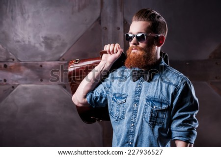 Stylishly confident. Handsome young bearded man in sunglasses looking away while holding a suitcase on his shoulder - stock photo