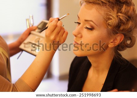 Stylist applying make up for bride on the wedding day  - stock photo