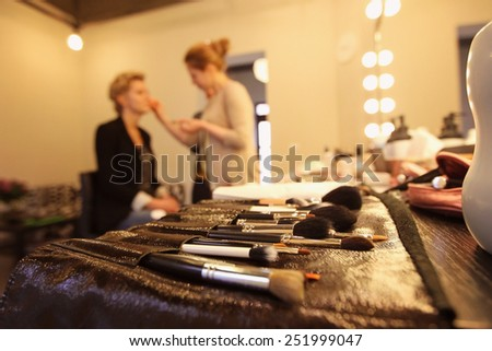 Stylist applying make up for bride on the wedding day with focus on the brushes - stock photo