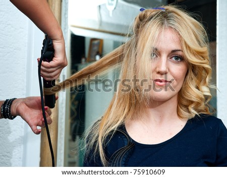 stylist curling woman hair and making new hairstyle in salon - stock photo