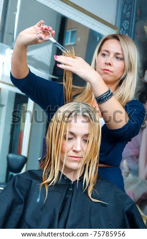 stylist cutting woman hair and making new hairstyle in salon - stock photo