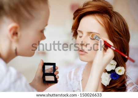 Stylist makes makeup bride before the wedding - stock photo