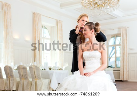 Stylist pinning up a bride's hairstyle before the wedding - stock photo