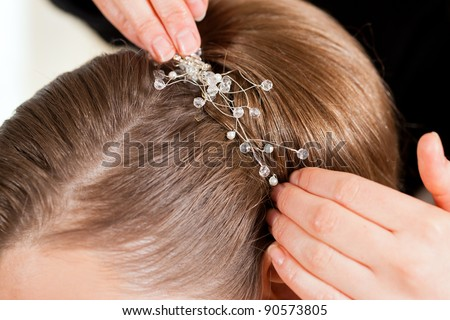 Stylist pinning up a bride's hairstyle before the wedding - close-up - stock photo