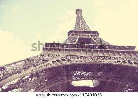 stylized aged photo of a Paris Eiffel Tower with cloudy skies - stock photo