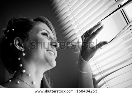 Stylized black and white photo ofl bride waits for groom near the window.  - stock photo