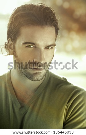 Stylized close portrait of a good looking man outdoors with a retro vintage feel and overall green sepia toning - stock photo