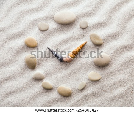 Stylized dial clock for pebble and shells arrows on the sand for concentration and relaxation for harmony and balance in pure simplicity - macro lens shot - stock photo