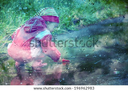 stylized photo of cute little girl is playing in muddy puddles - stock photo
