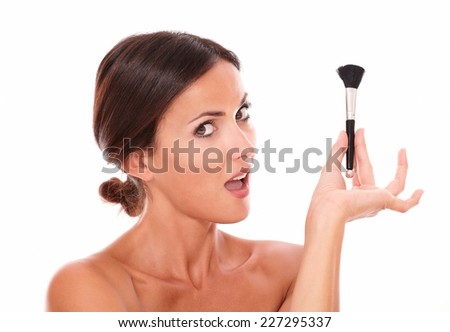 Stylized portrait of young woman with make up brush and nude shoulders looking at camera on isolated white background - stock photo