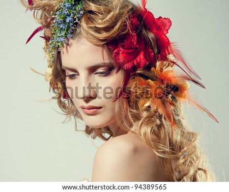 Stylized summer portrait of a young beautiful woman with flowers in her hair - stock photo