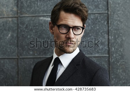 Suave man in spectacles and suit, looking away - stock photo