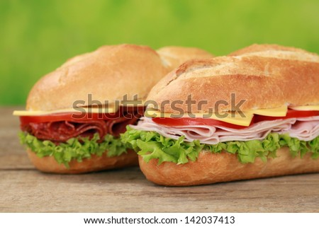 Sub Sandwiches with salami, ham, cheese, tomatoes and lettuce - stock photo