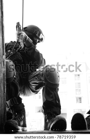 Subdivision anti-terrorist police during a black tactical exercises. Rope Techniques.  Real situation. Black and white photo with film grain. - stock photo