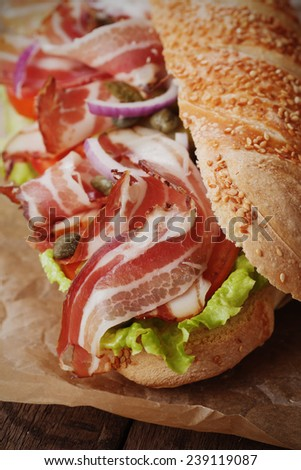 Submarine sandwich with bacon, pickles, tomato and lettuce salad - stock photo