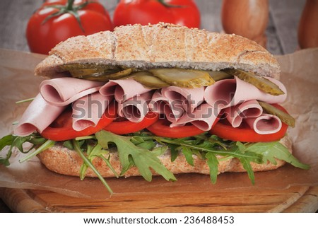 Submarine sandwich with baloney, pickles, tomato and rocket salad - stock photo
