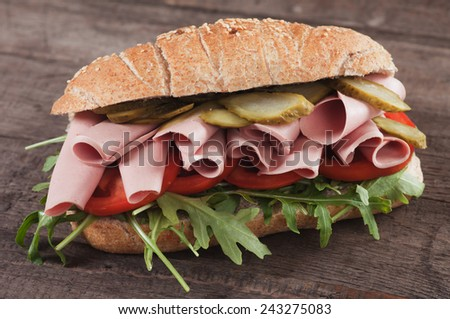 Submarine sandwich with bologna sausage, pickles, tomato and rocket salad - stock photo