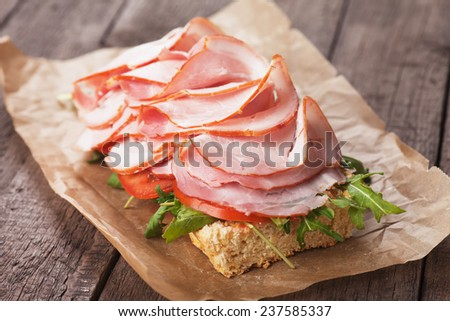 Submarine sandwich with smoked ham, tomato and lettuce salad - stock photo