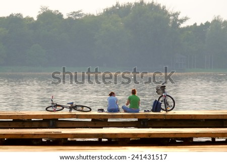 SUBOTICA, PALIC LAKE, SERBIA: two women with bikes are relaxing at the sunset on a wooden pier of Palic Lake near Subotica, Serbia. Shot in 2014 - stock photo