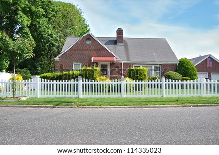Suburban Brick Home white picket fence American Flag residential neighborhood street - stock photo