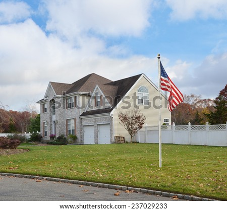 Suburban brick McMansion style home with two car garage white picket fence residential neighborhood blue sky clouds USA - stock photo