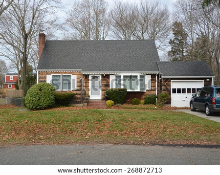 Suburban Brown wood Shingle Cape Cod style home Autumn day residential neighborhood USA - stock photo