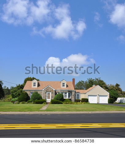 Suburban Bungalow Cottage Home in Residential Neighborhood on Two Lane Street with Yellow Traffic Line on Sunny Blue Sky Day - stock photo
