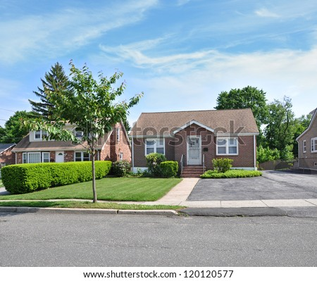 Suburban Bungalow Cottage Middle Class Home Sunny Blue Sky Day - stock photo