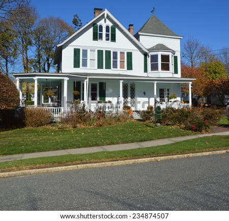 Suburban gable front of white and green Victorian style home in residential neighborhood clear blue sky USA - stock photo