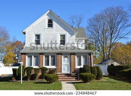Suburban gable front style home lamppost landscaped in residential neighborhood clear blue sky USA - stock photo