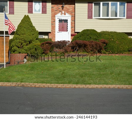 Suburban High Ranch brick landscaped home with cobble stone curb sunny autumn day residential neighborhood USA - stock photo