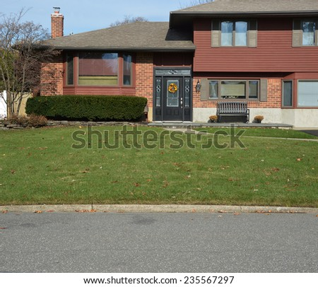 Suburban high ranch home entrance  landscaped front yard lawn in residential neighborhood USA - stock photo