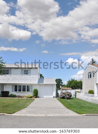 Suburban Home Brick Driveway Blooming Rhododendron Flower Bush Sunny Blue Sky Day with Clouds Residential Neighborhood USA - stock photo