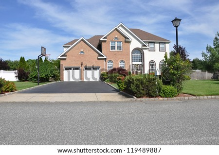 Suburban Home with Blacktop driveway and Two Car Garage in residential neighborhood sunny blue sky day - stock photo