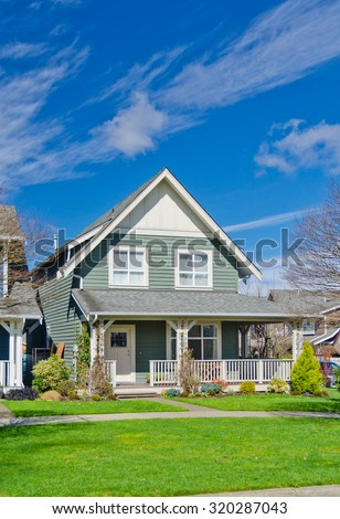 Suburban home with nicely landscaped and trimmed front yard lawn. Vertical. - stock photo
