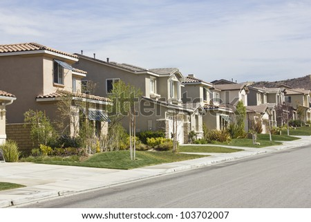 Suburban homes run upwards along a hill side. - stock photo