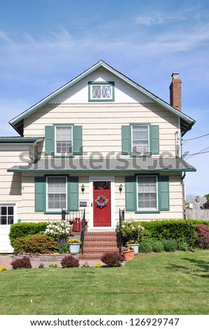 Suburban House Gable Style Architecture Landscaped with Pansies Flowers Plants Sunny Blue Sky Day - stock photo