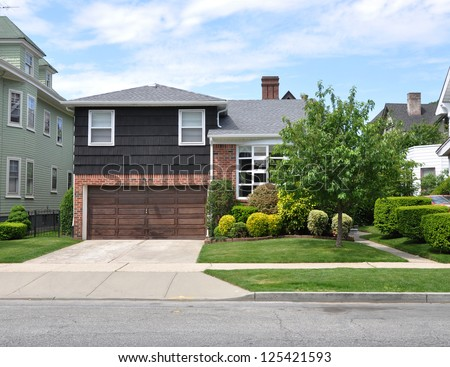 Suburban House Landscaped front yard lawn Residential Neighborhood USA Blue Sky Clouds - stock photo