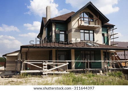 Suburban house under construction with large porch  - stock photo