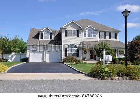 Suburban Luxury Two Story Two Car Garage Home Driveway Landscaped Front Yard Mailbox Street Light Lamp post - stock photo